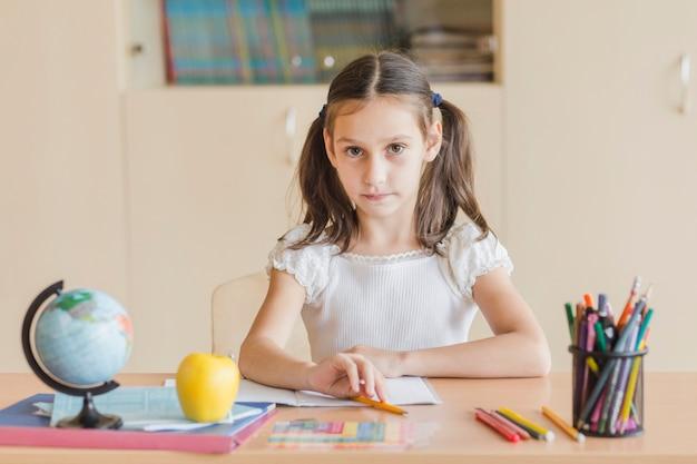 Mädchen, das am schreibtisch im klassenzimmer sitzt