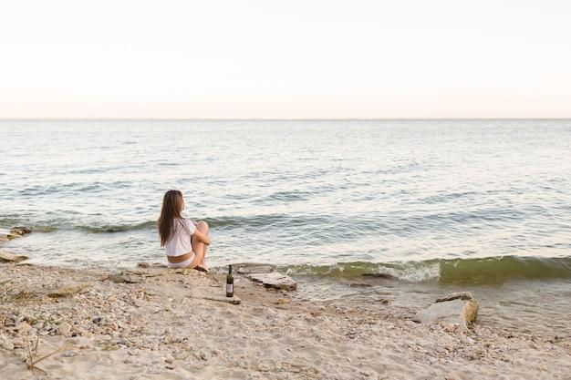 Mädchen, das am strand mit einer flasche wein sitzt Premium Fotos