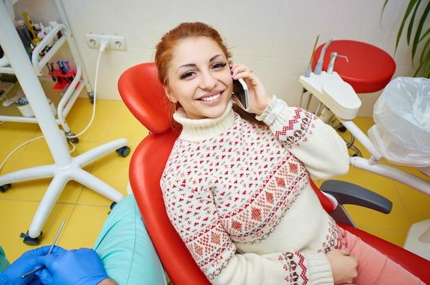 Mädchen, das am telefon im stuhl des zahnarztes spricht