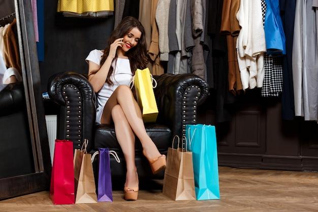 Mädchen, das am telefon spricht und im einkaufszentrum mit einkäufen sitzt.