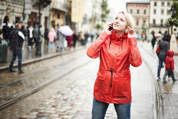Mädchen, das am telefon unter regen auf der straße spricht. porträt der hübschen lächelnden jungen frau im roten hellen regenmantel. sonniger regentag in der stadt