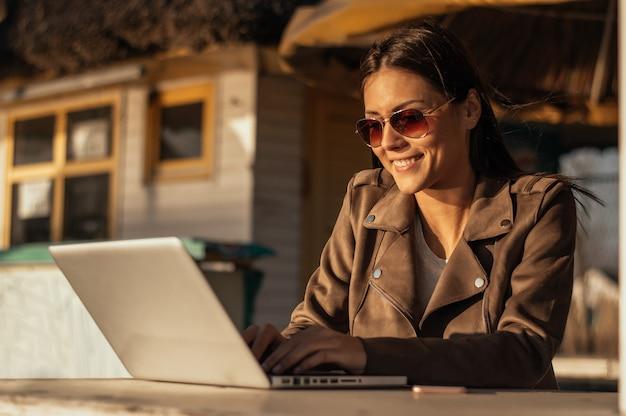 Mädchen, das an dem laptop im freien arbeitet