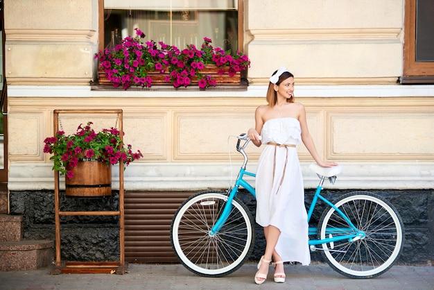 Mädchen, das an der alten stadt mit blauem retro- fahrrad der weinlese aufwirft