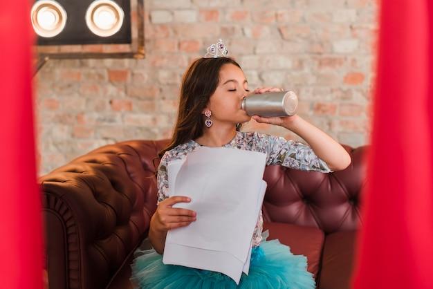 Mädchen, das an der bühne hinter dem vorhang hält scripts trinkwasser von der flasche sitzt