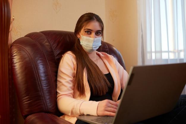 Mädchen, das an einem laptop arbeitet, der in einem stuhl sitzt