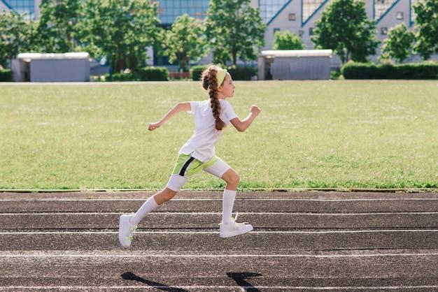 Mädchen, das an einem sonnigen sommerabend joggt, auf laufband, stadion, körperliches training, zurück zur schule legt.