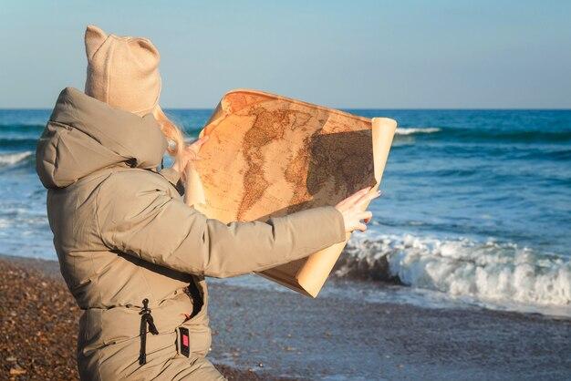 Mädchen, das an einem sonnigen wintertag eine karte am meer beobachtet