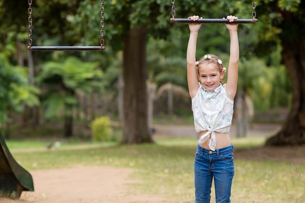 Mädchen, das an einem spielgerät im park hängt