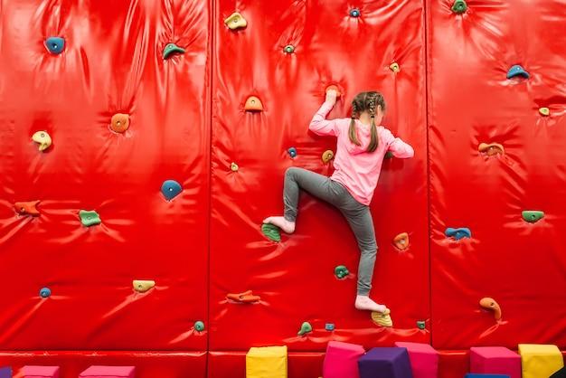 Mädchen, das an einer wand im kinderattraktionsspielplatz klettert. unterhaltungszentrum. glückliche kindheit