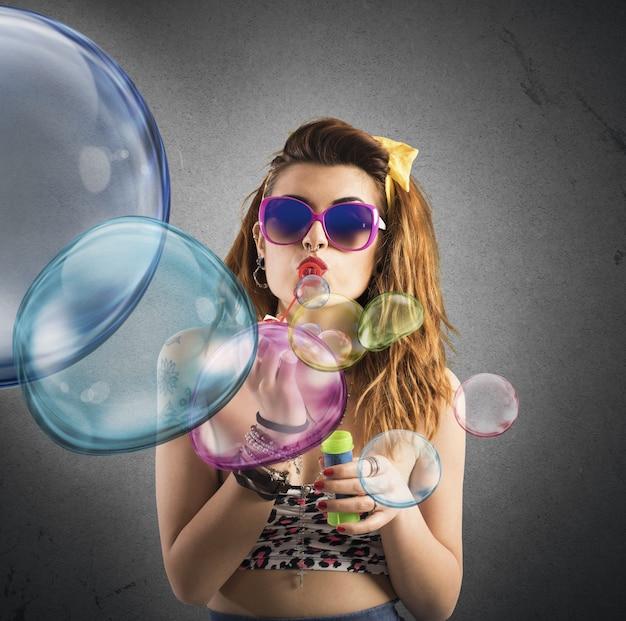 Mädchen, das an farbigen seifenblasen spielt