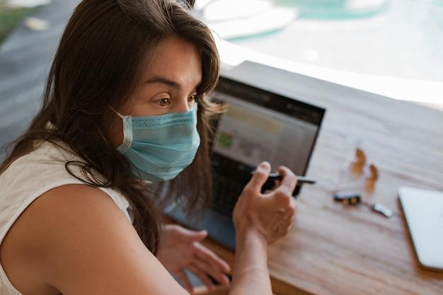 Mädchen, das an laptop in einer maske arbeitet. hochwertiges foto