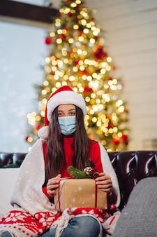 Mädchen, das an silvester ein weihnachtsgeschenk hält. mädchen, das die kamera betrachtet. weihnachten während des coronavirus, konzept