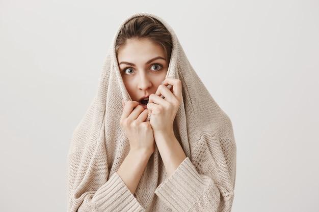 Mädchen, das angst sieht, pullover auf kopf ziehen und kamera ängstlich starren