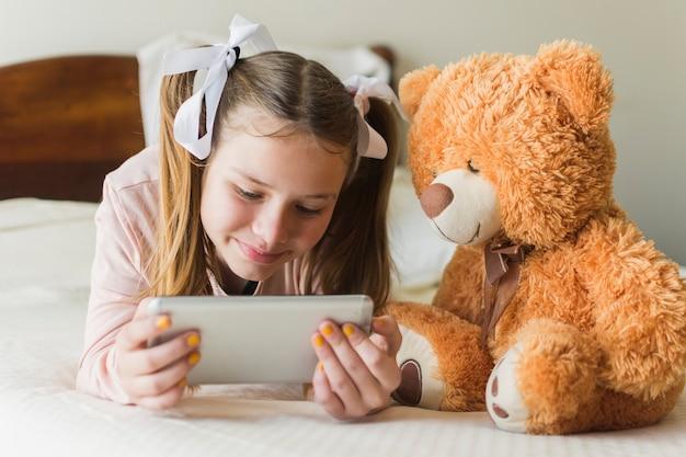 Mädchen, das auf bett mit dem teddybären betrachtet handy liegt
