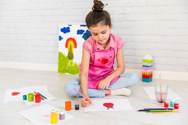 Mädchen, das auf bodenmalerei auf weißbuch mit farben sitzt