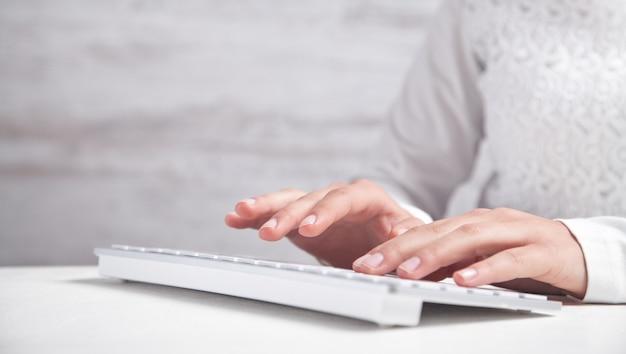 Mädchen, das auf computertastatur im schreibtisch schreibt.