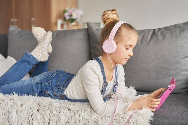 Mädchen, das auf couch in kopfhörern liegt und musik mit ihrem smarthphone hört