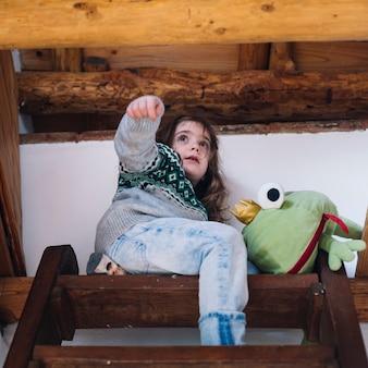 Mädchen, das auf das treppenhaus mit weichem spielzeug sitzt