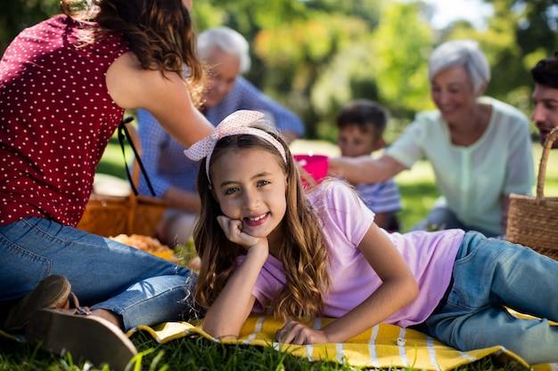 Mädchen, das auf decke neben familie ruht, die das picknick genießt