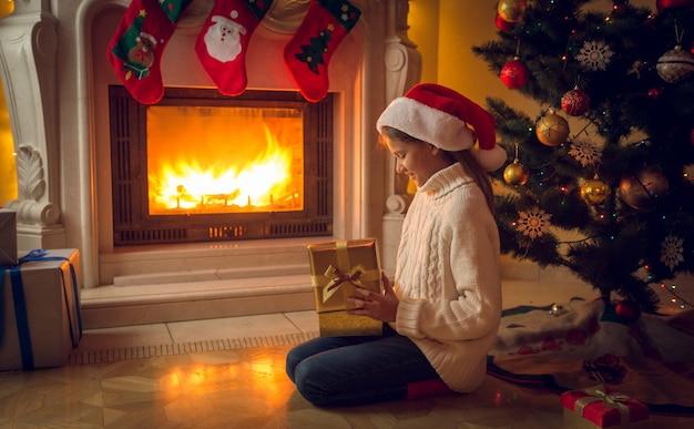 Mädchen, das auf dem boden am kamin sitzt und weihnachtsgeschenk in goldener schachtel erhält