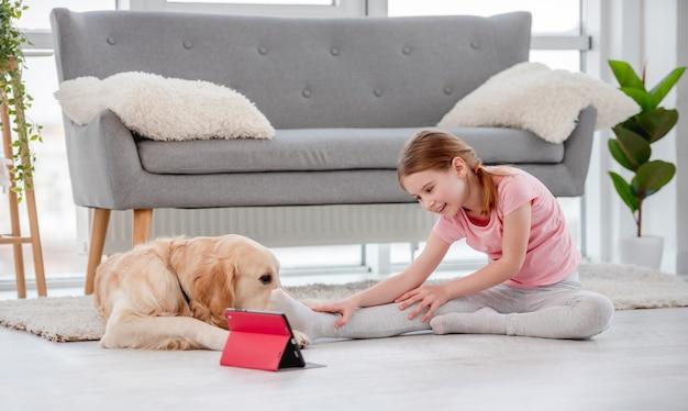 Mädchen, das auf dem boden mit goldenem retrieverhund sitzt und online mit tablette trainiert