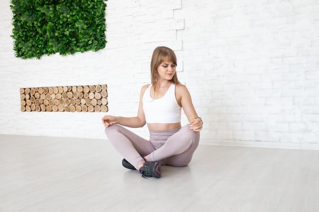 Mädchen, das auf dem boden nahe wand, yoga tuend sitzt