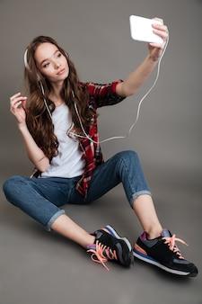 Mädchen, das auf dem boden sitzt und selfie mit kopfhörern nimmt