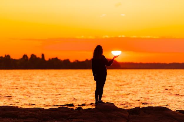 Mädchen, das auf dem felsen steht, der sonne zur hand hält. natur- und schönheitskonzept. orangefarbener sonnenuntergang. mädchensilhuette bei sonnenuntergang.