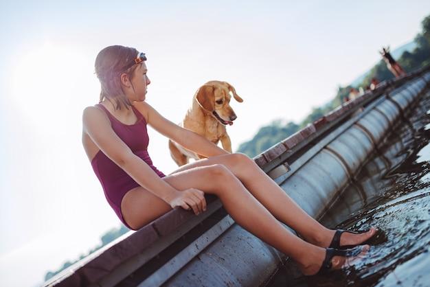 Mädchen, das auf dem flussdock mit ihrem hund sitzt