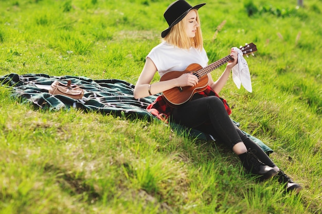 Mädchen, das auf dem gras sitzt und gitarre spielt
