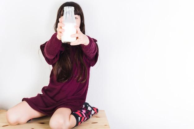 Mädchen, das auf dem hölzernen schreibtisch zeigt milchflasche sitzt