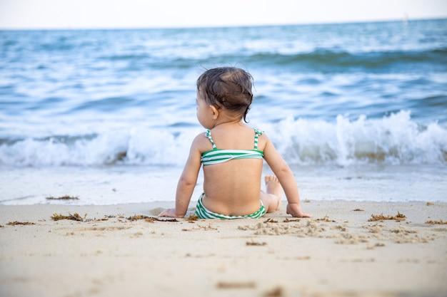 Mädchen, das auf dem sandstrand sitzt.