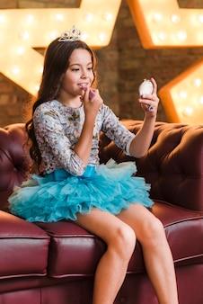 Mädchen, das auf dem sofa anwendet lippenstift gegen glühenden stern sitzt