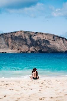 Mädchen, das auf dem strand aufpasst das meer sitzt