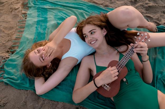 Mädchen, das auf dem strand lacht über ihren freund spielt ukulele liegt