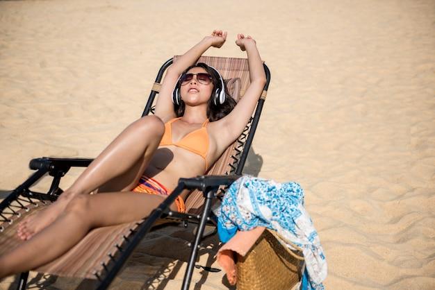 Mädchen, das auf dem strand vecation sich entspannt und musik mit kopfhörern hört