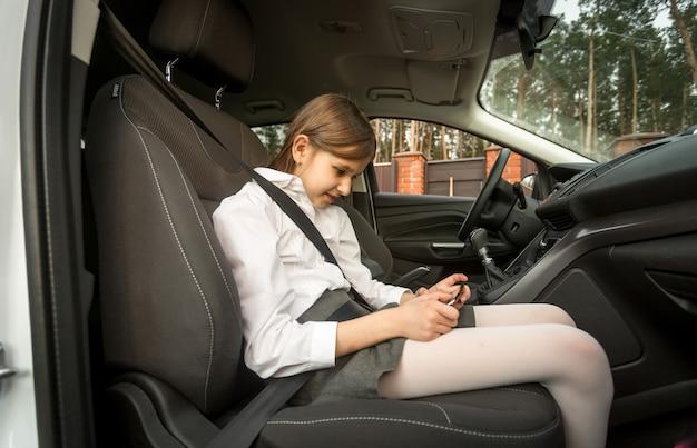 Mädchen, das auf dem vorderen autositz sitzt und handy benutzt