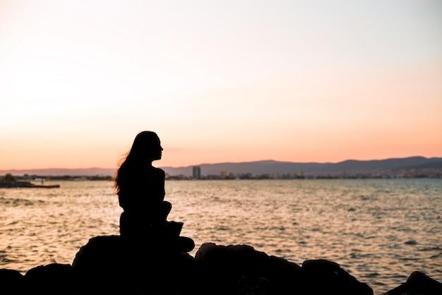 Mädchen, das auf den steinen am abendsonnenuntergang sittinng ist