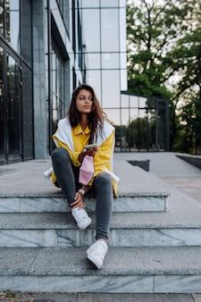 Mädchen, das auf den stufen ruht. attraktives modisches fröhliches trendiges hipster-mädchen, das stadtstraßen geht.