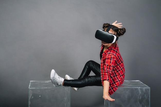 Mädchen, das auf den transparenten blöcken trägt schutzbrillen der virtuellen realität gegen grauen hintergrund sitzt