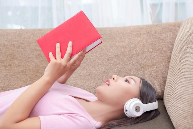 Mädchen, das auf der couch hört musik und liest bücher liegt.