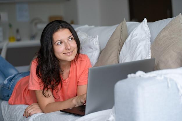 Mädchen, das auf der couch liegt, freut sich, den laptop betrachtend. lächeln, gute laune, gefühl der freude.