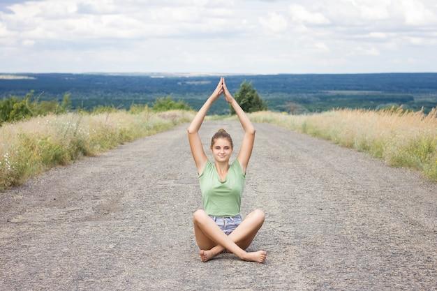 Mädchen, das auf der pflasterung meditiert. junges schönes mädchen, das in der natur erwägt. vorderansicht
