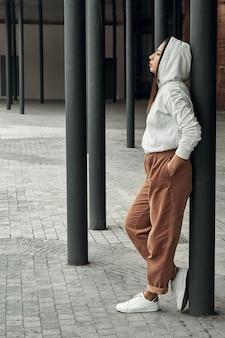 Mädchen, das auf der straße nahe schwarzen säulen aufwirft. wandern und unterhaltung in der stadt.