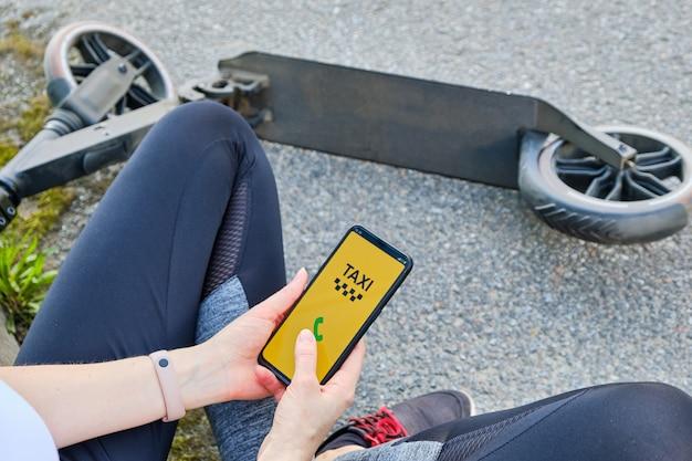 Mädchen, das auf der straße sitzt, ruft ein taxi durch die anwendung auf einem smartphone