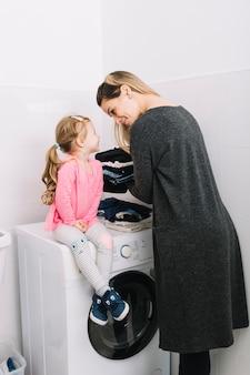 Mädchen, das auf der waschmaschine betrachtet ihre mutter sitzt