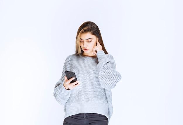 Mädchen, das auf die nachrichten oder kommentare auf ihrem smartphone schaut.
