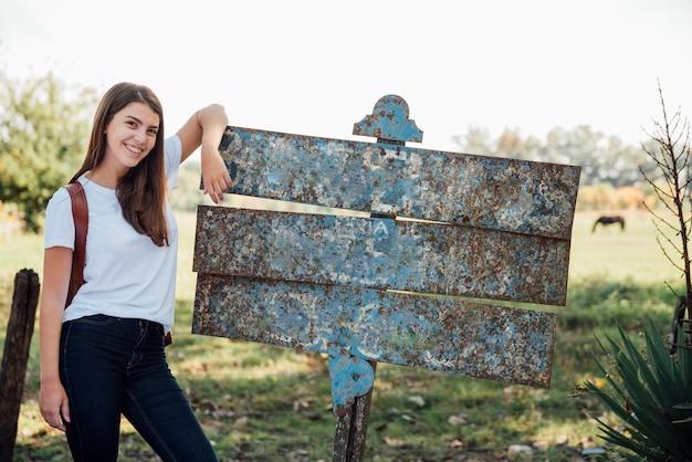 Mädchen, das auf einem alten metallstraßenschild stillsteht