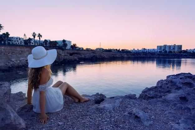 Mädchen, das auf einem aufpassenden sonnenuntergang des ufers steht. schöner strand auf einer tropischen insel. zypern protaras