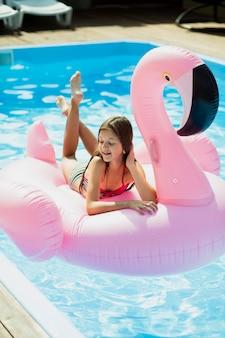 Mädchen, das auf einem flamingo floatie sitzt und unten schaut